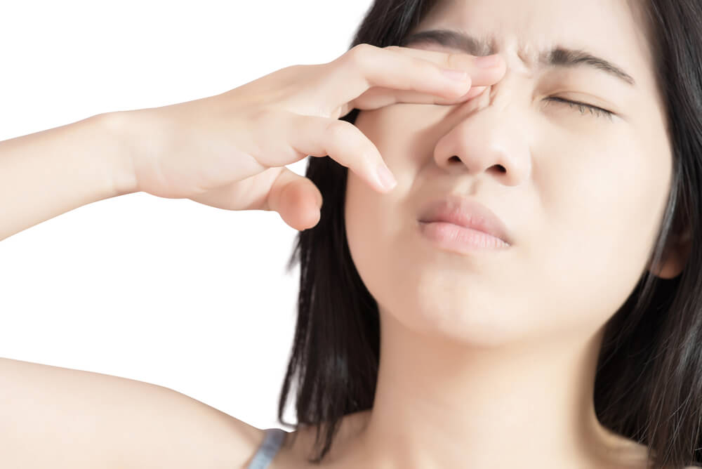 Young woman with hand on her sore eye